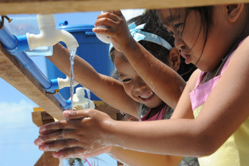 Children smile as they wash their hands at a Plan International installed water pump