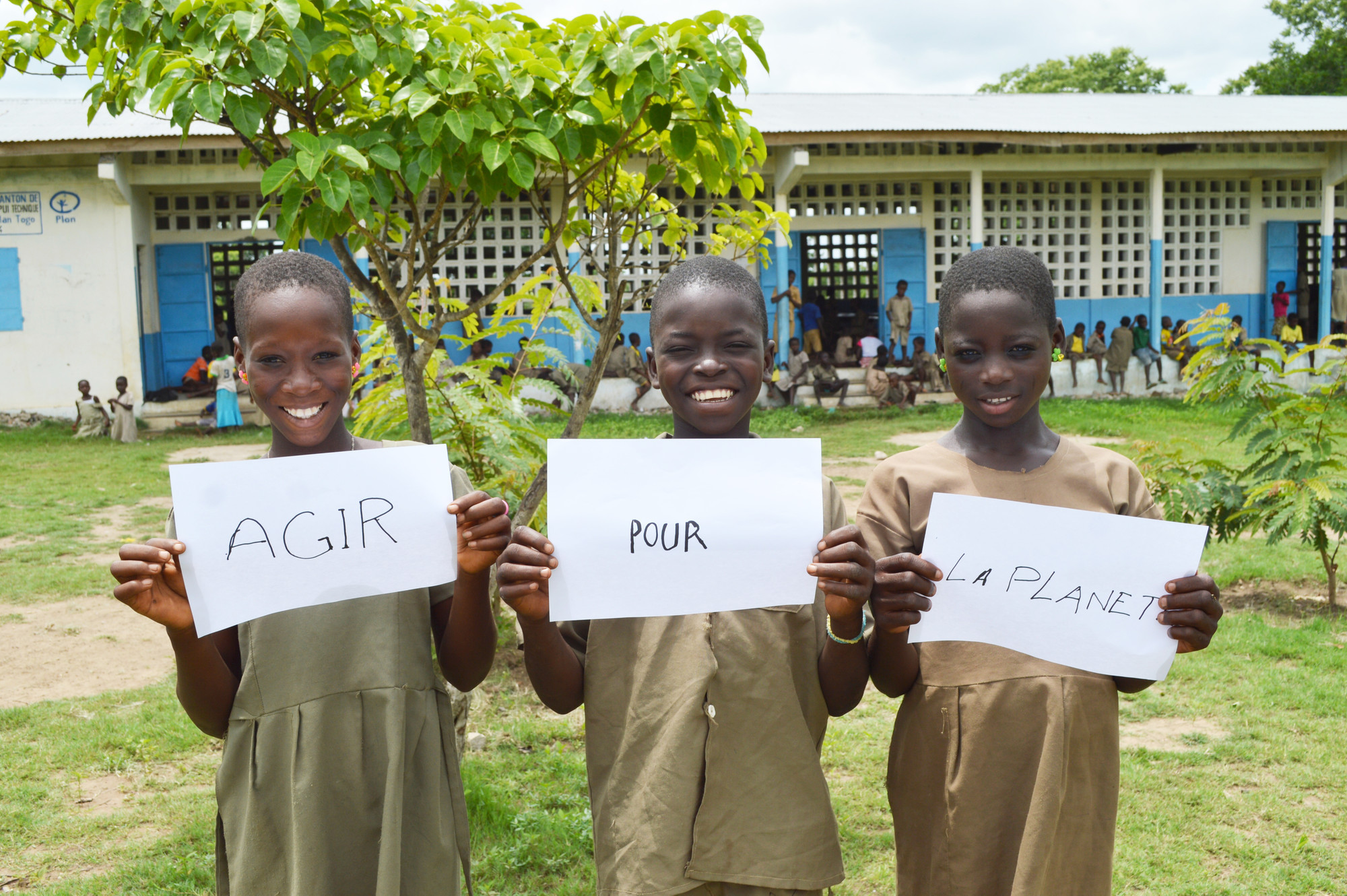 Girls in Togo hold up signs reading act for the planet