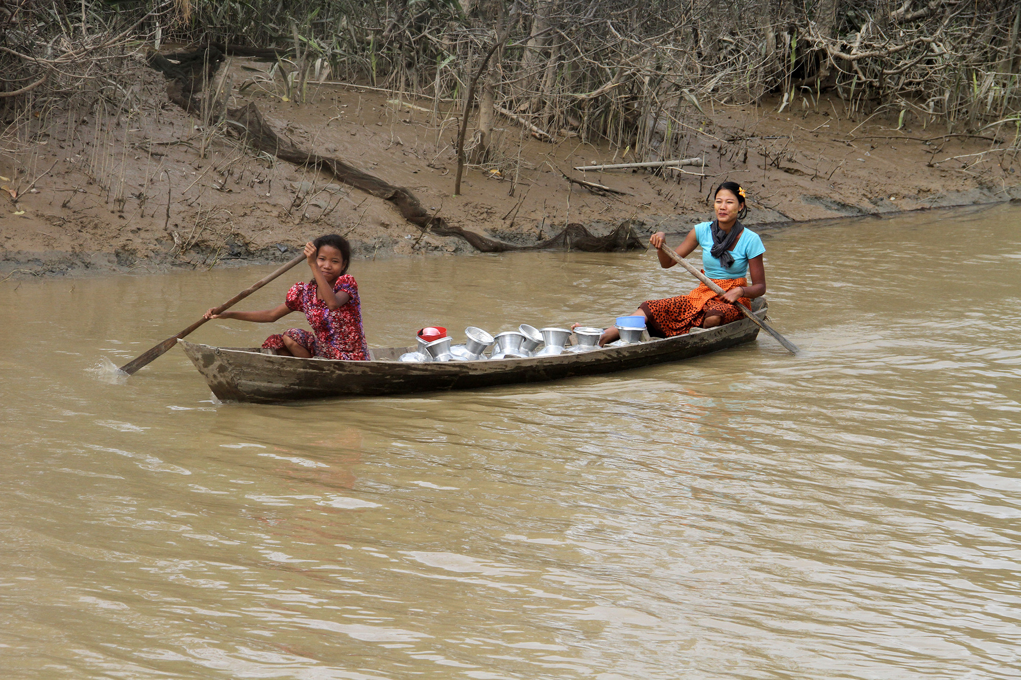 Girls paddle through flood water