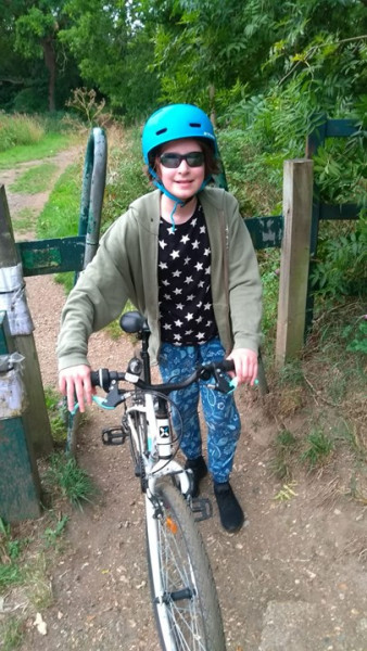 Ella on her bike cycling 30 miles to raise money for Plan International UK