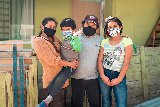 Photo of a family standing together wearing masks