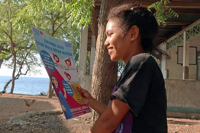 A girl looks at one of our child protection posters