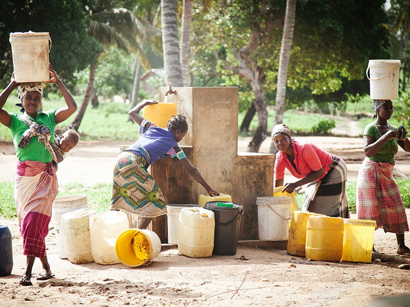 women collecting water in shade