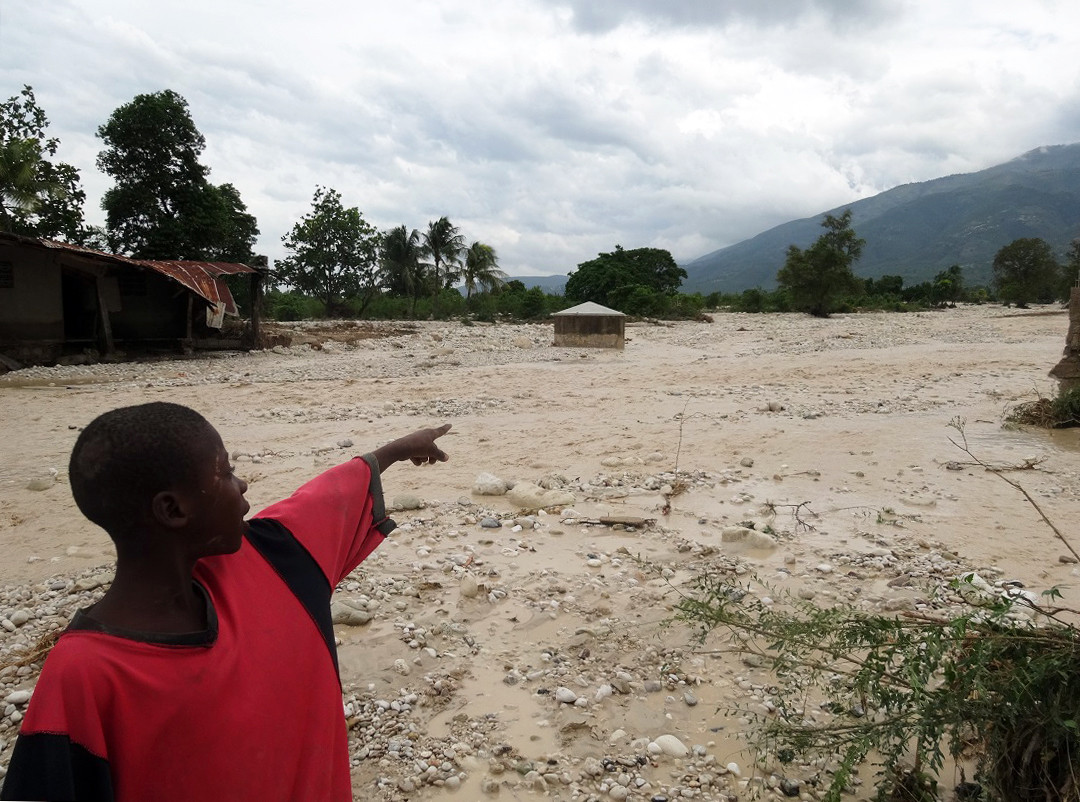 Rosemikas brother points to his family home destroyed by the floods after the Haiti hurricane