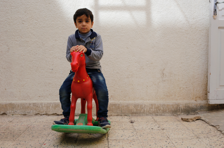 Syrian refugee child plays on a rocking horse