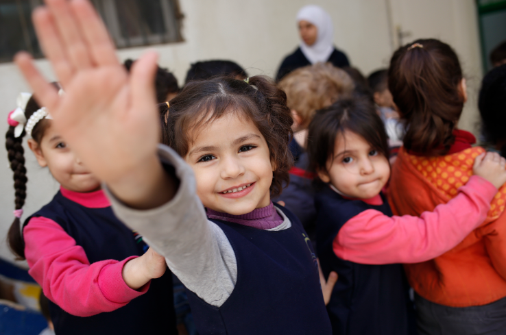 Syrian refugee child waves during school