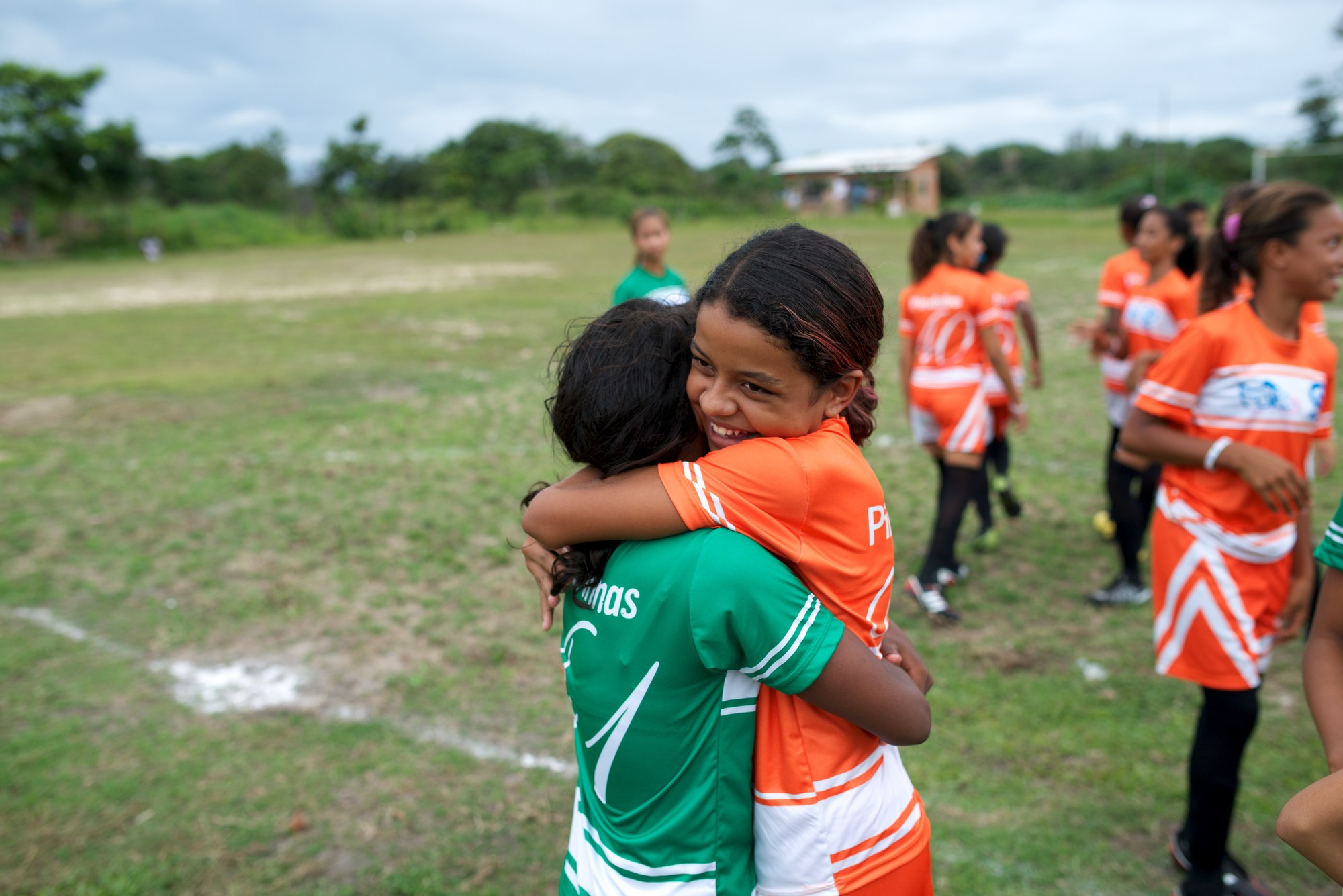 Girls playing football have a hug at half time