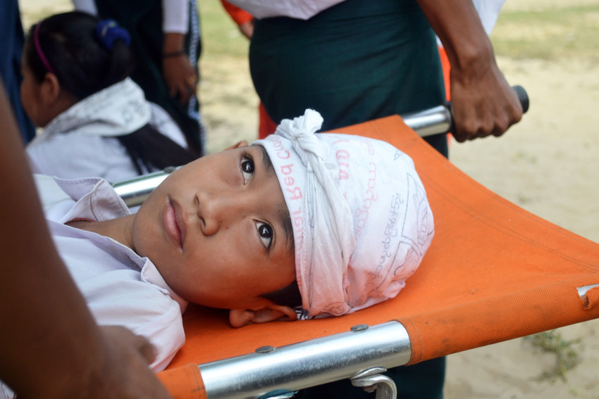 A school child pretending to be injured during a disaster simulation exercise