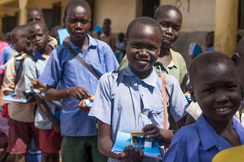 Children receive new school supplies during distribution in Yei