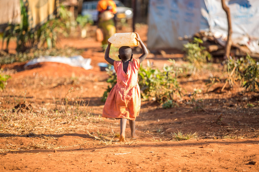 girl carrying large water container