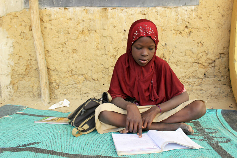 Girl reading book at temporary camp for people displaced by violence in Niger's Diffa region