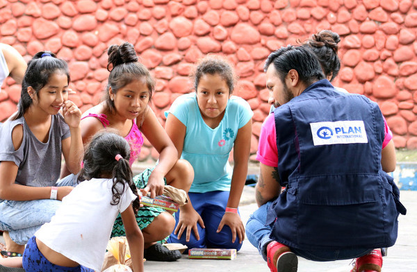 A Plan International employee works with children at a shelter in Guatemala