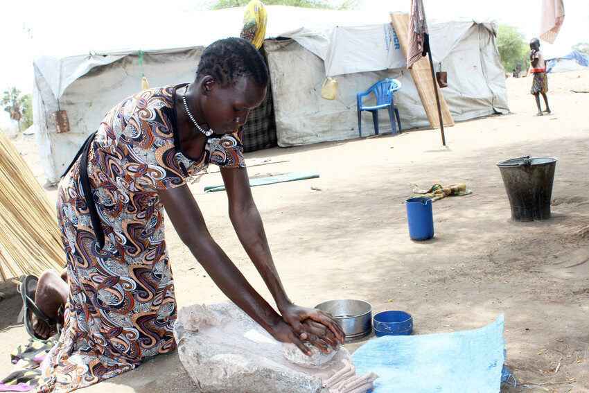 A woman grinds grain for a meal in South Sudan