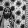 Ghana-Ayisha stands before a traditional piece of Ghanaian cloth on the clothing line in the compound