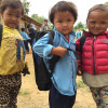 Children stand outside a school built by Plan International