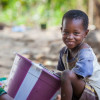 A smiling boy with a bucket in Guinea