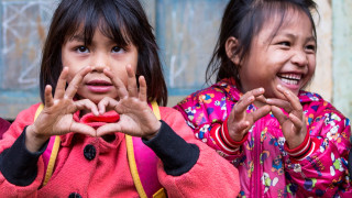 Girls making heart shape with their hands in Vietnam