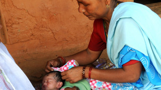 Community healthcare worker in Nepal helps a woman with a newborn baby