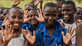 Rwandan children waving - Pay in your fundraising money for Plan International UK