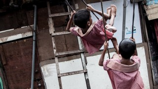 Young boys use a makeshift swing in Mumbai slum