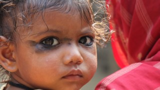 Young girl held by mother nepal