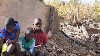 A family in front of the ruins of their home in Zimbabwe
