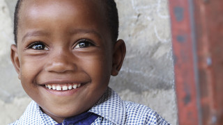 A boy smiles at an Early Childhood Care Centre in Tanzania