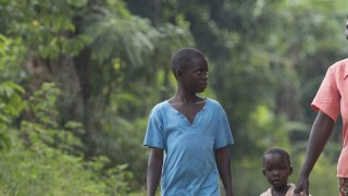 A photograph of Babuza walking with her three children