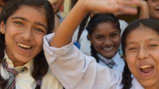 Children wave at a school supported by Plan International in Nepal.