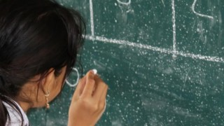 A girl writes on a blackboard