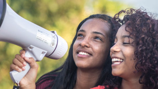 Two girls hold a megaphone