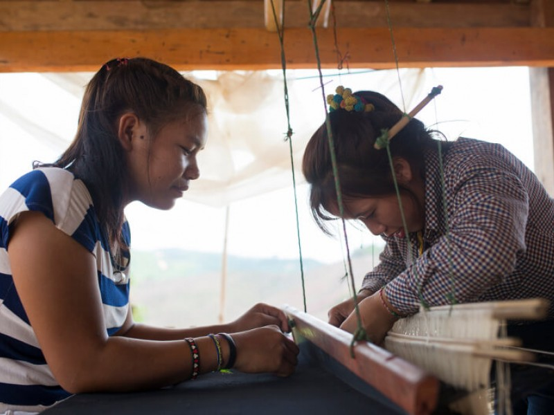Girls learning traditional weaving techniques